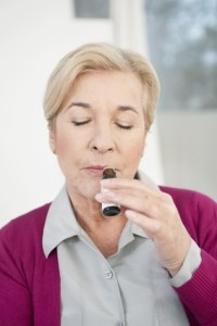 close-up of a woman smelling aromatherapy oil