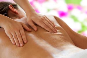 Zwei Hände massarieren Rücken